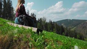 Μια νέα καυκάσια γυναίκα με ένα σακίδιο πλάτης κάθεται σε μια κορυφή σύνδεσης ενός βουνού και βάζει σε ένα καπέλο Η έννοια φιλμ μικρού μήκους