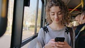 Μια νέα κυρία Using ένα Smartphone στο λεωφορείο στοκ εικόνα με δικαίωμα ελεύθερης χρήσης
