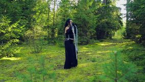Μια νέα μάγισσα στα μαύρα ενδύματα, που απελευθερώνονται από τις αλυσίδες, χορεύει με τους στις δασικές αποκριές Ύφος Gothick απόθεμα βίντεο