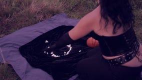 Μια νέα μάγισσα στο Μαύρο δημιουργεί με τις άσπρες πέτρες αποκριές Ύφος Gothick απόθεμα βίντεο
