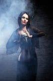 Μια νέα μάγισσα brunette που κρατά ένα ανθρώπινο κρανίο Στοκ Εικόνα