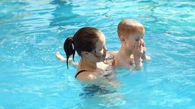 Μια νέα μητέρα διδάσκει το γιο της για να βουτήξει στο νερό στη λίμνη, σε αργή κίνηση φιλμ μικρού μήκους