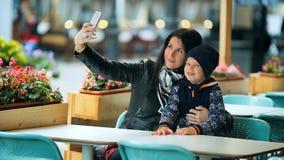 Μια νέα μητέρα κάνει selfie με την λίγο χαριτωμένο γιο σε έναν πίνακα σε έναν καφέ φιλμ μικρού μήκους