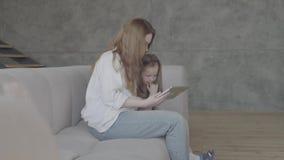 Μια νέα μητέρα και λίγη κόρη με τη μακρυμάλλη συνεδρίαση μαζί στον καναπέ στο καθιστικό που χρησιμοποιεί την ταμπλέτα _ απόθεμα βίντεο