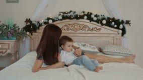 Μια νέα μητέρα και ο γιος της που βρίσκονται στο κρεβάτι απόθεμα βίντεο
