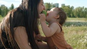 Μια νέα μητέρα και ο γιος της τρώνε ένα μήλο Ένα μικρό παιδί δαγκώνει ένα μήλο απόθεμα βίντεο