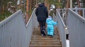 Μια νέα μητέρα και το μικρό παιδί της περπατούν επάνω τα σκαλοπάτια απόθεμα βίντεο