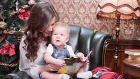 Μια νέα μητέρα με έναν μικρό γιο κάθεται σε μια πολυθρόνα δέρματος από το χριστουγεννιάτικο δέντρο και εξετάζει ένα βιβλίο παιδιώ απόθεμα βίντεο