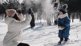 Μια νέα μητέρα με έναν νέο γιο τριών χρονών παίζει με το χιόνι σε ένα χειμερινό πάρκο Το Mom κυμάτισε τα όπλα της και έριξε απόθεμα βίντεο