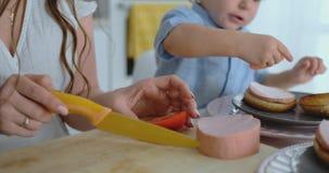 Μια νέα μητέρα με ένα μικρό παιδί έκοψε μαζί με ένα μαχαίρι μια ντομάτα για σπιτικό burger Υγιής μάγειρας τροφίμων από κοινού απόθεμα βίντεο