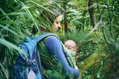 Μια νέα μητέρα με ένα μωρό σε μια σφεντόνα περπατά στη ζούγκλα Στοκ φωτογραφία με δικαίωμα ελεύθερης χρήσης
