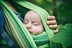 Μια νέα μητέρα με ένα μωρό σε μια σφεντόνα περπατά στη ζούγκλα Στοκ Φωτογραφίες