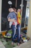 Μια νέα μητέρα με τα γυαλιά κρατά δύο μικρά παιδιά Στοκ εικόνα με δικαίωμα ελεύθερης χρήσης