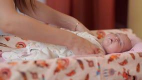 Μια νέα μητέρα παίρνει ένα μικρό παιδί ύπνου στα όπλα της μικρά moms παιδιών Ευτυχία απόθεμα βίντεο