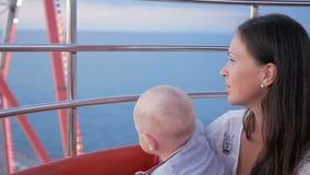 Μια νέα μητέρα παρουσιάζει στο γιο της όμορφη πόλη με ένα ύψος ροδών Ferris Το παιδί επιθεωρεί όλοι γύρω Το αγόρι είναι 1 έτος φιλμ μικρού μήκους