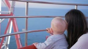 Μια νέα μητέρα παρουσιάζει στο γιο της όμορφη πόλη με ένα ύψος ροδών Ferris Το παιδί επιθεωρεί όλοι γύρω Το αγόρι είναι 1 έτος απόθεμα βίντεο