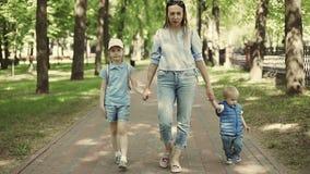 Μια νέα μητέρα περπατά σε ένα πάρκο με τα παιδιά κίνηση αργή φιλμ μικρού μήκους