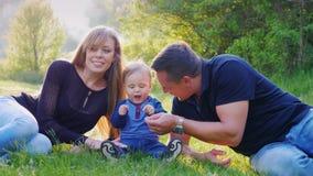 Μια νέα οικογένεια με ένα παιδί στηρίζεται στο πάρκο Παιχνίδι με το αγοράκι σας, ενός έτους βρέφος απόθεμα βίντεο