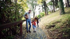 Μια νέα οικογένεια με τα παιδιά που περπατούν στο πάρκο το φθινόπωρο o απόθεμα βίντεο