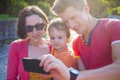 Μια νέα οικογένεια παίρνει μια φωτογραφία Στοκ εικόνα με δικαίωμα ελεύθερης χρήσης