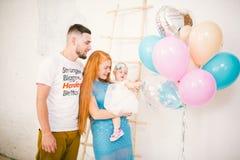 Μια νέα οικογένεια τριών ανθρώπων, mom μπαμπάς ` s και ενός έτους βρέφος κορών ` s στέκεται μέσα στο δωμάτιο Κράτημα ενός μπαλονι στοκ εικόνες με δικαίωμα ελεύθερης χρήσης