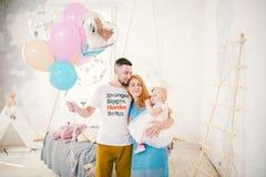 Μια νέα οικογένεια τριών ανθρώπων, mom μπαμπάς ` s και ενός έτους βρέφος κορών ` s στέκεται μέσα στο δωμάτιο Κράτημα ενός μπαλονι στοκ φωτογραφίες με δικαίωμα ελεύθερης χρήσης