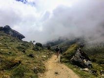 Μια νέα ομάδα διεθνών οδοιπόρων, που οδηγείται από τον τοπικό οδηγό Inca τους, πλοηγεί τα βουνά των Άνδεων μέσω των σύννεφων στοκ εικόνες με δικαίωμα ελεύθερης χρήσης