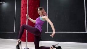 Μια νέα προκλητική προκλητική γυναίκα χορού, ένας πολυ χορός χορού στην αίθουσα γύρω από τον πόλο Στοκ Εικόνες