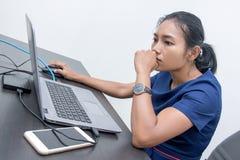 Μια νέα στοχαστική γυναίκα εξετάζει ένα lap-top στοκ εικόνες με δικαίωμα ελεύθερης χρήσης
