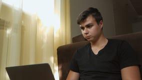 Μια νέα συνεδρίαση τύπων σε ένα δωμάτιο στο πάτωμα από το παράθυρο χρησιμοποιεί ένα lap-top Ένα freelancer με μια σοβαρή έκφραση  φιλμ μικρού μήκους