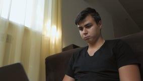 Μια νέα συνεδρίαση τύπων σε ένα δωμάτιο στο πάτωμα από το παράθυρο χρησιμοποιεί ένα lap-top Ένα freelancer με μια σοβαρή έκφραση  απόθεμα βίντεο