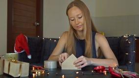 Μια νέα συσκευασία γυναικών παρουσιάζει Παρόν που τυλίγεται στο έγγραφο τεχνών με μια κόκκινη και χρυσή κορδέλλα για τα Χριστούγε απόθεμα βίντεο
