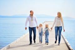 Μια νέα, φιλική οικογένεια: ο πατέρας, μητέρα και δύο κόρες είναι W στοκ εικόνες
