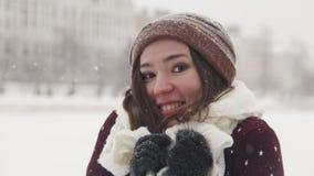 Μια νέα χαμογελώντας γυναίκα που στέκεται το χειμώνα έξω Φθορά του άσπρου μαντίλι στοκ φωτογραφία με δικαίωμα ελεύθερης χρήσης