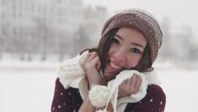 Μια νέα χαμογελώντας γυναίκα που στέκεται το χειμώνα έξω Φορώντας το άσπρο μαντίλι και σχετικά με το με τα χέρια της στοκ εικόνα