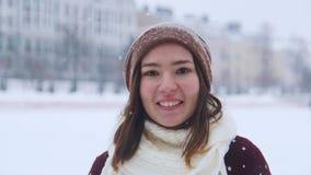 Μια νέα χαμογελώντας γυναίκα που στέκεται το χειμώνα έξω στοκ φωτογραφία με δικαίωμα ελεύθερης χρήσης
