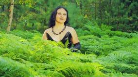 Μια νέα χαμογελώντας μάγισσα στα μαύρα ενδύματα στέκεται σε ένα δάσος σε ένα αλσύλλιο της φτέρης αποκριές Ύφος Gothick απόθεμα βίντεο