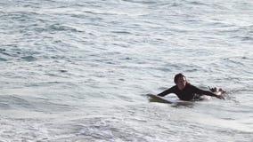 Μια νέα όμορφη γυναίκα κολυμπά στον ωκεανό στην ιστιοσανίδα της φιλμ μικρού μήκους