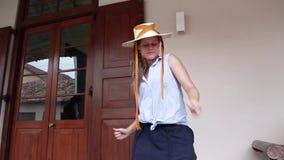 Μια νέα όμορφη γυναίκα σε ένα καπέλο αχύρου είναι wacky χοροί χορού στην οδό φιλμ μικρού μήκους