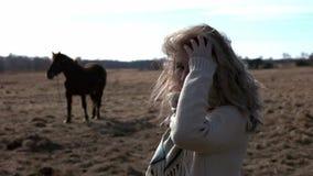 Μια νέα όμορφη γυναίκα φροντίζει για και γύροι το άλογό της φιλμ μικρού μήκους
