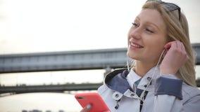 Μια νέα όμορφη ξανθή γυναίκα ακούει τη μουσική στο smartphone της χρησιμοποιώντας τα ακουστικά Μια νέα γυναίκα απολαμβάνει έναν π απόθεμα βίντεο
