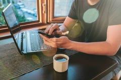 Μια νεολαία άτομο-blogger-επανδρώνει freelancer την εργασία σε ένα lap-top σε έναν καφέ στη Ιστανμπούλ και την κλήση τηλεφωνικώς  Στοκ Εικόνα