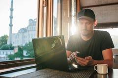 Μια νεολαία άτομο-blogger-επανδρώνει freelancer την εργασία σε ένα lap-top σε έναν καφέ στη Ιστανμπούλ και την κλήση τηλεφωνικώς  Στοκ φωτογραφία με δικαίωμα ελεύθερης χρήσης