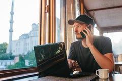Μια νεολαία άτομο-blogger-επανδρώνει freelancer την εργασία σε ένα lap-top σε έναν καφέ στη Ιστανμπούλ και την κλήση τηλεφωνικώς  Στοκ εικόνα με δικαίωμα ελεύθερης χρήσης