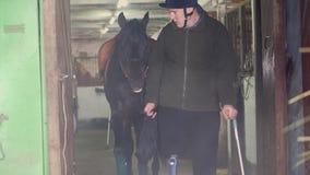 Μια νεολαία καθιστούσε ανίκανος jockey ατόμων τους μολύβδους από το σταύλο ένα μαύρο thoroughbred άλογο το άτομο έχει μια πρόσθεσ φιλμ μικρού μήκους