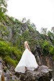 Μια νεολαία ξανθή σε έναν κομψό θέτει τους εναγκαλισμούς hem ενός φορέματος μπουντουάρ στα βουνά που στέκονται σε ένα επικίνδυνο  στοκ εικόνα με δικαίωμα ελεύθερης χρήσης