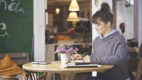 Μια νεολαία που χαμογελά το χαριτωμένο κορίτσι brunette είναι lookin στο τηλέφωνο στοκ φωτογραφίες