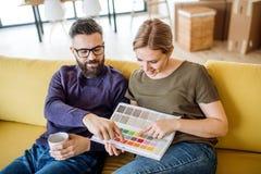Μια νεολαία συνδέει με τα δείγματα χρώματος καθμένος στον καναπέ, που κινείται στο νέο σπίτι στοκ φωτογραφίες
