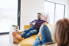 Μια νεολαία συνδέει με τη συνεδρίαση καφέ στον καναπέ, που κινείται στο νέο σπίτι στοκ φωτογραφία με δικαίωμα ελεύθερης χρήσης