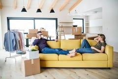 Μια νεολαία συνδέει με τη συνεδρίαση καφέ στον καναπέ, που κινείται στο νέο σπίτι στοκ φωτογραφίες